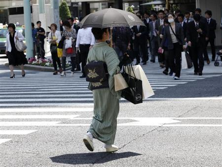 A woman in a traditional ''Kimono'' carries shopping bags at a shopping district in Tokyo May 19, 2011. REUTERS/Kim Kyung-Hoon