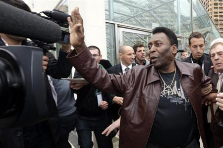 Brazilian soccer player legend Edison Arantes do Nascimento (R), known as Pele, waves to fans and media as he arrives on the Soccer Footprints promenade dedicated to the greatest football players in Monaco in this October 17, 2012 file photo. REUTERS/Eric Gaillard