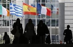 Люди проходят мимо флагов Ирландии, Греции, Испании и Франции у здания Европарламента в Брюсселе 3 мая 2013 года. Страны Евросоюза и Европарламент достигли в среду предварительного соглашения о долгосрочном бюджете ЕС в размере 960 миллиардов евро, но ратификация сделки немедленно была поставлена под сомнение законодателем-социалистом. REUTERS/Francois Lenoir