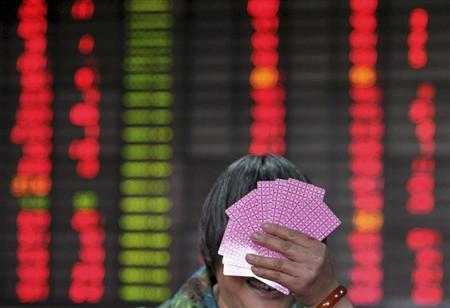 An investor covers her face with playing cards as she reacts to a photojournalist in front of an electronic board showing stock information at a brokerage house in Nanjing, Jiangsu province, May 3, 2013. REUTERS/Stringer