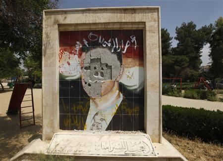 A vandalised mosaic picture of Syria's President Bashar al-Assad is pictured in Raqqa province, east Syria in this May 1, 2013 file photo. REUTERS/Hamid Khatib/Files