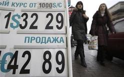 Женщины проходят мимо пункта обмена валют в Санкт-Петербурге 13 июня 2009 года. Рубль торгуется у годового минимума к корзине валют, отражая повсеместный выход из рискованных и сырьевых активов в ответ на заявленные Федрезервом намерения начать сокращение стимулирующих программ уже в этом году, а также на очередные сигналы о замедлении китайского промсектора. REUTERS/Alexander Demianchuk