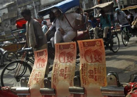 Cycle rickshaws move past a display of rupees at a roadside currency exchange stall in the old quarters of Delhi June 10, 2013. REUTERS/Anindito Mukherjee