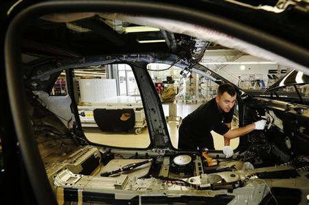 Employee Chris Corrie fixes the main wiring loom into a Rolls Royce Ghost at the Rolls Royce Motor Cars factory at Goodwood near Chichester in southern England April 24, 2013. REUTERS/Luke MacGregor