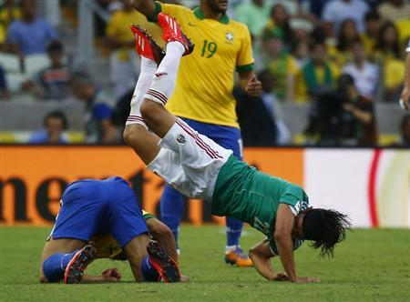 Mexico's Gerardo Flores (R) and Brazil's Fred fall after a challenge during their Confederations Cup Group A match at the Estadio Castelao in Fortaleza June 19, 2013. REUTERS/Kai Pfaffenbach