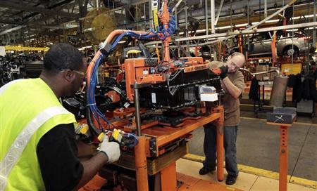 Ford Assembly workers install a battery onto the chassis of a Ford Focus Electric vehicle at the Michigan Assembly Plant in Wayne, Michigan November 7, 2012. REUTERS/Rebecca Cook