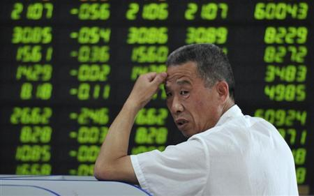 An investor looks back in front of an electronic board showing stock information filled with green-coloured figures, which indicate falling prices, at a brokerage house in Fuyang, Anhui province June 20, 2013. REUTERS/China Daily