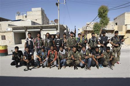 Kurdish fighters from the Popular Protection Units (YPG) pose for a picture in Aleppo's Sheikh Maqsoud neighbourhood, June 7, 2013. REUTERS/Muzaffar Salman