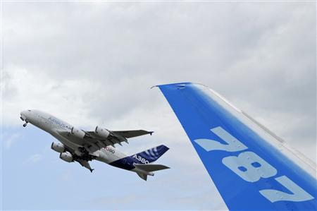 The vertical stabilizer of a Boeing 787 Dreamliner is seen as an Airbus A380, the world's largest jetliner, takes off during the 49th Paris Air Show at the Le Bourget airport near Paris in this June 23, 2011, file photo. REUTERS/Gonzalo Fuentes/Files
