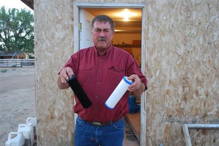 Jeff Locker, a Wyoming farmer, displays water filters from his well on September 17, 2009. REUTERS/Jon Hurdle