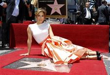 Singer and actress Jennifer Lopez poses on her star after it was unveiled on the Walk of Fame in Hollywood, California June 20, 2013. REUTERS/Mario Anzuoni