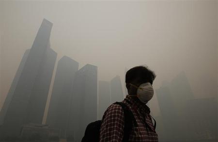 6月20日、インドネシアでの野焼きによる煙がシンガポールなどに流れ込んでいる問題で、シンガポールのリー・シェンロン首相は、大気汚染が数週間以上続く可能性があると述べた。写真は21日撮影(2013年 ロイター/Edgar Su)