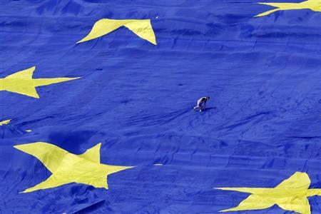 An organiser walks on a large European Union flag displayed in front of Romania's Parliament Building to mark EU Day in Bucharest May 9, 2013. REUTERS/Bogdan Cristel