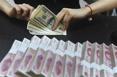 图为合肥一家银行的职员在清点美元钞票,手边是捆扎好的人民币现钞。REUTERS/Stringer/Files