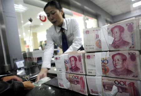 An employee hands Renminbi banknotes to a customer at a branch of the Industry and Commercial Bank of China in Hefei, Anhui province October 9, 2008. REUTERS/Stringer