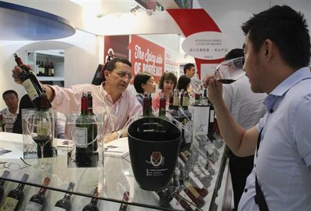 A salesman displays a bottle of French Cotes de Bourg wine to a customer at a wine expo in Beijing, June 4, 2013. REUTERS/Stringer