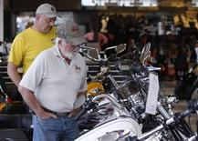 Customers look at the showroom inventory at Harley-Davidson of Frederick in Frederick Maryland in this October 23, 2012 file photo. Unless the Milwaukee-based company began to attract younger riders and penetrate new markets, analysts warned the waning of its overwhelmingly white, male and middle-aged base would hurt sales in North America, where it still earns two-thirds of its revenue. REUTERS/Gary Cameron/Files