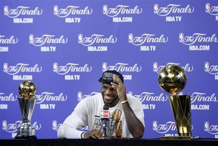 Miami Heat's LeBron James sits with the Larry O'Brien Trophy and the Bill Russell MVP Trophy after his team defeated the San Antonio Spurs in Game 7 to win the NBA Finals basketball playoff in Miami, Florida June 20, 2013. REUTERS/Mike Segar
