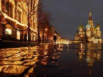 Мужчина идет по Красной площади мимо ГУМа 26 ноября 2007 года. Уикенд в Москве обещает быть облачным и принести в российскую столицу небольшие дожди и, возможно, грозы. REUTERS/Oksana Yushko