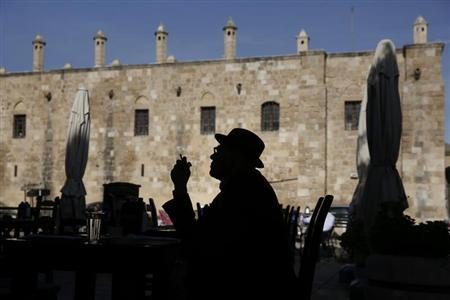 A man smoking a cigarette is silhouetted in front of Buyuk Han (The Great Inn) in Nicosia, Northern Cyprus March 25, 2013. REUTERS/Yorgos Karahalis