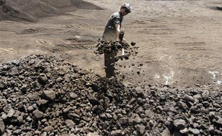 A worker shovels coal at a yard in the western Indian city of Ahmedabad March 22, 2012. REUTERS/Amit Dave/Files