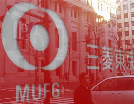 A pedestrian is reflected on a logo of Bank of Tokyo-Mitsubishi UFJ in Tokyo December 13, 2012. REUTERS/Yuriko Nakao