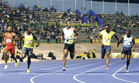 Usain Bolt (C) crosses the finish line ahead of (L-R) Asafa Powell, Nickel Ashmeade, Kamar Baley-Cole, and Nesta Garter to win the 100m men's final of the JAAA National Senior Trials, which determines the team to represent Jamaica in the IAAF World Championships Moscow, in Kingston June 21, 2013. REUTERS/Gilbert Bellamy