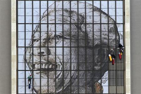 Rope access technicians work to complete a huge portrait of former South African President Nelson Mandela on the windows of the Civic Centre building in Cape Town, June 15, 2013. REUTERS/Mark Wessels