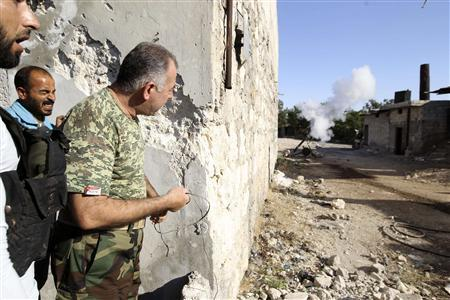 Colonel Abdul-Jabbar al-Aqidi, commander of the rebels' Military Council in Aleppo, launches a mortar shell at the frontline in the Al-Sakhour neighborhood of Aleppo, June 21, 2013. REUTERS/Muzaffar Salman
