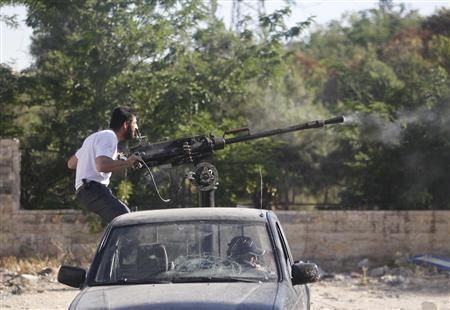 A Free Syrian Army fighter fires a machine gun at the frontline in the Al-Sakhour neighborhood of Aleppo, June 21, 2013. REUTERS/Muzaffar Salman