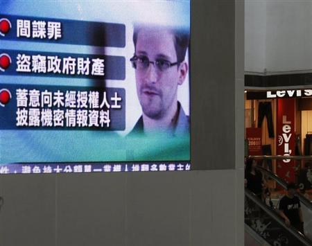 A monitor broadcasts news on the charges against Edward Snowden, a former contractor at the National Security Agency (NSA), by the United States, at a shopping mall in Hong Kong June 22, 2013. REUTERS/Bobby Yip