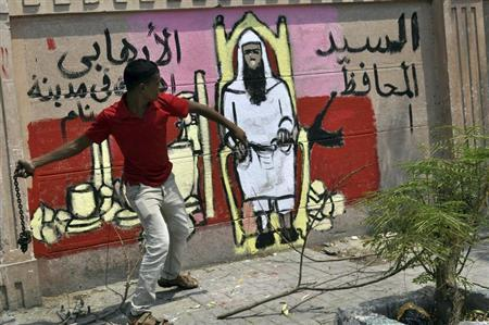 A protester throws a chain next to a graffiti on the wall depicting the newly appointed governor of Luxor Adel Mohamed al-Khayat, as a terrorist, as protests gather in front of the goverorate building to protest his appointment in Luxor, June 19, 2013. REUTERS/Stringer