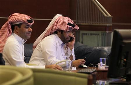 Brokers monitor a screen displaying stock market index at an investment bank in Riyadh, June 9, 2013. REUTERS/Faisal Al Nasser