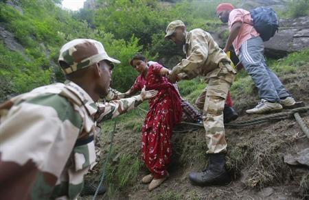 Soldiers assist a woman during rescue operations in Govindghat in the Himalayan state of Uttarakhand June 23, 2013. REUTERS/Danish Siddiqui