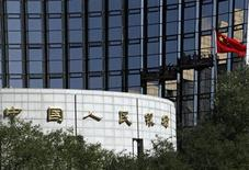 A Chinese national flag flies as workers clean the windows of the headquarters of the People's Bank of China, the country's central bank, in Beijing October 10, 2012. REUTERS/Barry Huang
