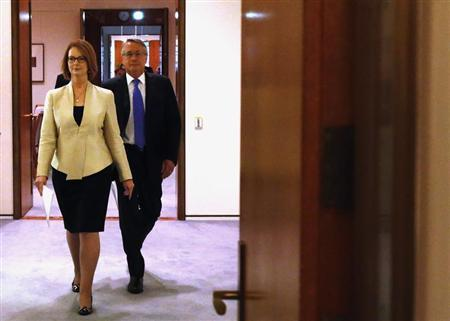 Australian Prime Minister Julia Gillard (L) walks into the Cabinet Room with Treasurer Wayne Swan at Parliament House in Canberra May 13, 2013. REUTERS/David Gray