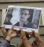 Демонстранты держат фотографию Эдварда Сноудена возле консульства США в Гонконге 13 июня 2013 года. Бывший сотрудник ЦРУ Эдвард Сноуден, которому на родине предъявлены обвинения в госизмене, прилетел в воскресенье в Москву из Гонконга и запросил политическое убежище в Эквадоре. REUTERS/Bobby Yip