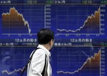 Мужчина проходит мимо брокерской конторы в Токио 23 мая 2013 года. Доллар поднялся до пика 2,5 недель к валютной корзине и растет к иене на фоне ожиданий сокращения стимулирующей программы ФРС. REUTERS/Toru Hanai
