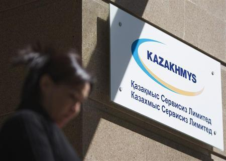 A woman walks past the logo of mining group Kazakhmys, at the company's office in Almaty May 15, 2013. REUTERS/Shamil Zhumatov