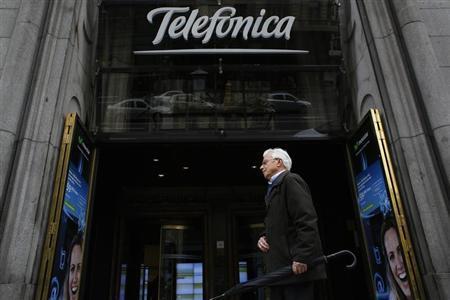 A man walks past Telefonica's building in central Madrid March 26, 2013. REUTERS/Juan Medina