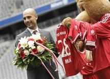 Pep Guardiola, novo técnico do Bayern de Munich recebe do mascote do time uma camisa oficial com o nome de sua filha Maria, no estádio Allianz Arena, em Munique. O bem-sucedido Bayern de Munique apresentou nesta segunda-feira seu novo treinador, Pep Guardiola, num grande evento midiático para o time bávaro, que busca manter a hegemonia nacional e continental. 24/06/2013. REUTERS/Michaela Rehle