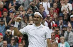 O suiço Roger Federer comemora vitória sobre o romeno Victor Hanescu of Romania em partida válida pelo torneio de tênis de Wimbledon, em Londres. Federer iniciou a defesa de seu título em Wimbledon com uma vitória fácil sobre o romeno Victor Hanescu na partida de abertura do Centre Court nesta segunda-feira. 24/06/2013. REUTERS/Stefan Wermuth