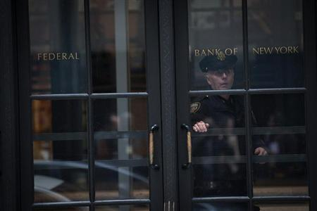 A Federal Reserve Police officer looks out of the door as he stands guard inside the New York Federal Reserve Building in New York, October 17, 2012. REUTERS/Keith Bedford