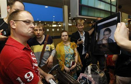 Journalists show an iPad with the picture of Edward Snowden, former contractor for the U.S. National Security Agency, to passengers of a flight from Hong Kong trying to find out if Snowden was aboard the plane, in Moscow's Sheremetyevo airport, June 23, 2013. REUTERS/Sergei Karpukhin