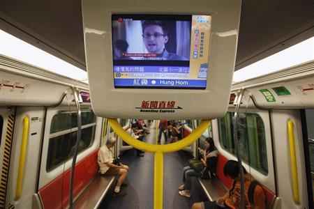 Edward Snowden, a former contractor at the National Security Agency (NSA), is seen during a news broadcast on a screen inside a train in Hong Kong June 18, 2013. REUTERS/Bobby Yip