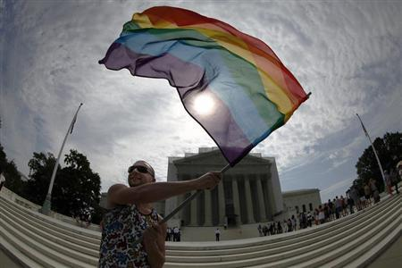 Gay marriage supporter Vin Testa waves a rainbow flag in anticipation of U.S. Supreme Court rulings in the cases against California's gay marriage ban known as Prop 8 and the 1996 federal Defense of Marriage Act (DOMA), outside the court building in Washington, June 24, 2013. REUTERS/Jonathan Ernst