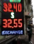 Вывеска пункта обмена валюты в Санкт-Петербурге 3 октября 2011 года. Рубль подешевел в начале торгов вторника, отразив отрицательную динамику сырьевых и развивающихся рынков в ответ на риски ухудшения ситуации в банковской системе Китая, чреватой замедлением его экономического роста и спроса на сырье. REUTERS/Alexander Demianchuk