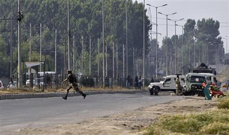 An Indian army soldier runs for cover at the scene of an encounter with separatist militants in Srinagar June 24, 2013. REUTERS/Danish Ismail