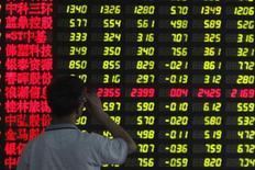 Инвестор в брокерской конторе в Шанхае 25 июня 2013 года. Центробанк Китая одобрил план запуска новой пилотной программы, разрешающей отдельным домохозяйствам осуществлять финансовые инвестиции за рубежом, сообщили официальные СМИ во вторник. REUTERS/Aly Song