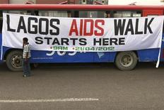 A man walks past a banner tied on a bus before the start of a charity walk on HIV/AIDS at the Ebute Mata district in Nigeria's commercial capital Lagos April 21, 2012. REUTERS/Akintunde Akinleye